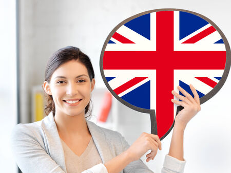 english girl: education, foreign language, english, people and communication concept - smiling woman holding text bubble of british flag Stock Photo