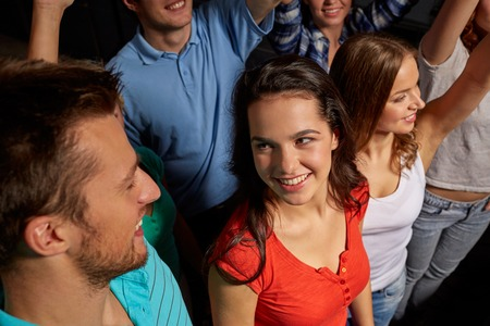 nightclub crowd: party, holidays, celebration, nightlife and people concept - smiling friends waving hands at concert in club