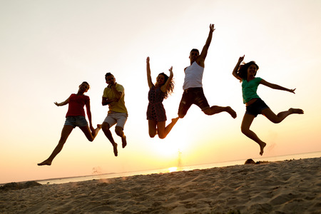 people having fun: friendship, summer vacation, holidays, party and people concept - group of smiling friends dancing and jumping on beach Stock Photo