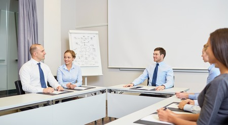 consulting room: business, people and teamwork concept - group of smiling businesspeople meeting in office Stock Photo