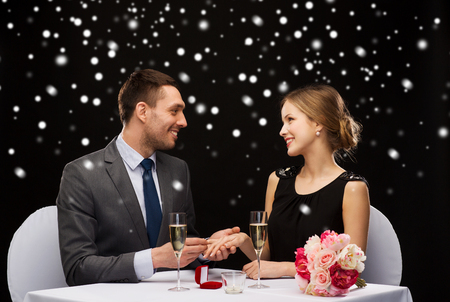 celebration, christmas, holidays and people concept - smiling couple with red gift box and ring at restaurant over black snowy background photo