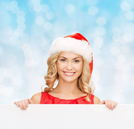 christmas, x-mas, people, advertisement and sale concept - happy woman in santa helper hat with blank white board over blue lights background photo