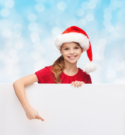 christmas, holidays, people, advertisement and sale concept - happy little girl in santa helper hat with blank white board over blue lights background photo