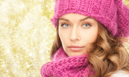yellow fleece: happiness, winter holidays, christmas and people concept - close up of young woman in pink hat and scarf over yellow lights background Stock Photo
