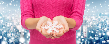 christmas, holidays and people concept - close up of woman in pink sweater holding snowflake over snowy city background photo