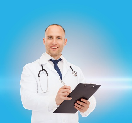 laser light: medicine, profession and healthcare concept - smiling male doctor with clipboard and stethoscope writing prescription over blue background