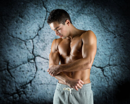 arm pain: pain, sport, bodybuilding, health and people concept - young male bodybuilder touching injured elbow over concrete wall background