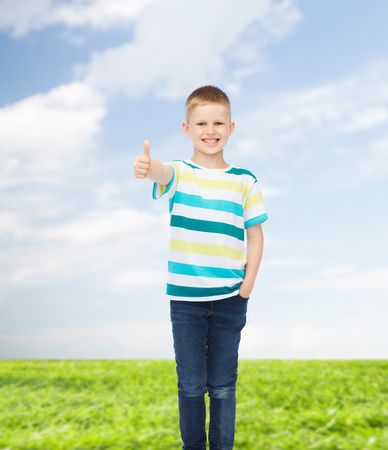 pre approval: happiness, childhood, environment and people concept - smiling little boy in casual clothes showing thumbs up over natural background Stock Photo