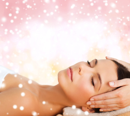 beauty, health, holidays, people and spa concept - beautiful woman in spa salon getting face or head massage over pink background Foto de archivo