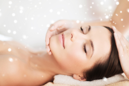 smooth skin: beauty, health, people and spa concept - beautiful young woman in spa salon lying on the massage desk Stock Photo