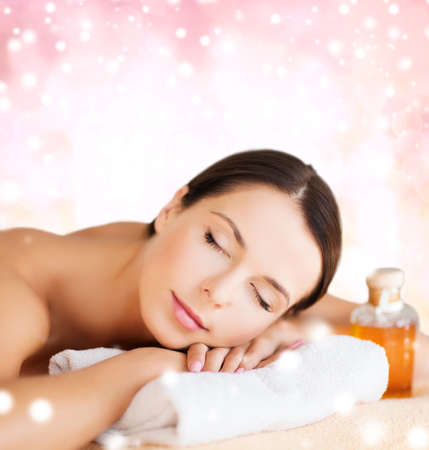 body oil: beauty, health, people and spa concept - beautiful young woman with body oil in spa over pink background