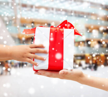 gift giving: holidays, present, christmas, childhood and happiness concept - close up of child and mother hands with gift box over shopping center background Stock Photo
