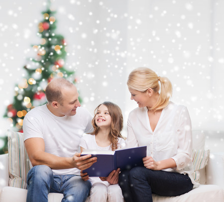 beautiful preteen girl: family, childhood, holidays and people - smiling mother, father and little girl reading book over living room and christmas tree background