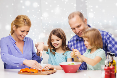 a little dinner: food, family, children, happiness and people concept - happy family with two kids making dinner at home