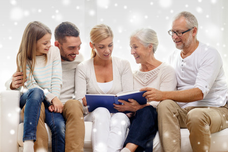 family, happiness, generation and people concept - happy family with book or photo album sitting on couch at home Stock Photo