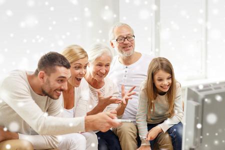 familia, la felicidad, la generación y la gente concepto - la familia feliz que se sienta en el sofá y viendo la televisión en casa