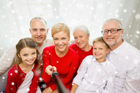 taking photo: family, holidays, generation, christmas and people concept - smiling family with camera and selfie stick taking picture at home Stock Photo