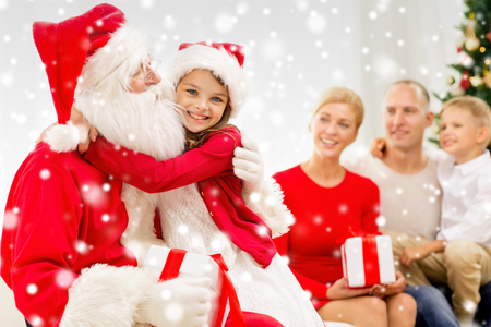 grateful: family, holidays, generation, christmas and people concept - smiling family with santa claus and gift boxes at home Stock Photo