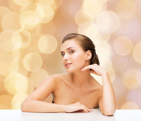 jeune fille adolescente nue: la beaut�, le concept de la sant� et les gens - en souriant belle femme avec une peau parfaite propre sur fond beige lumi�res