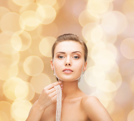 beauty, people and jewelry concept - beautiful woman with pearl earrings and necklace over beige lights background