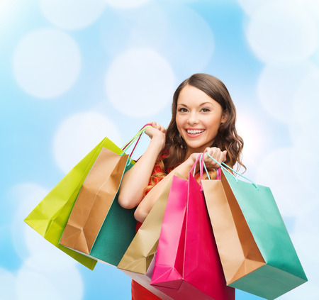 sale, gifts, christmas, holidays and people concept - smiling woman with colorful shopping bags over blue lights background photo