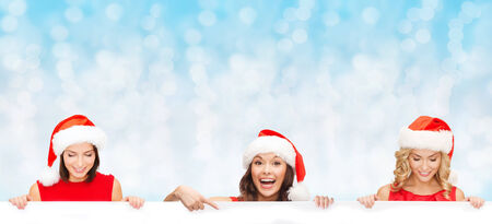 christmas, x-mas, people, advertisement and sale concept - happy women in santa helper hat with blank white board over blue lights background photo