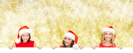 christmas, x-mas, people, advertisement and sale concept - happy women in santa helper hat with blank white board over yellow lights background photo