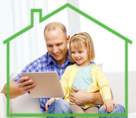 ahorro energetico: familia, la paternidad, la tecnología y la gente concepto - feliz padre e hija con la computadora Tablet PC en casa detrás de símbolo de la casa verde