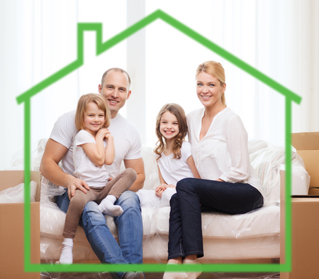 family, children, accommodation and home concept - smiling parents and two little girls at home behind green house symbol photo