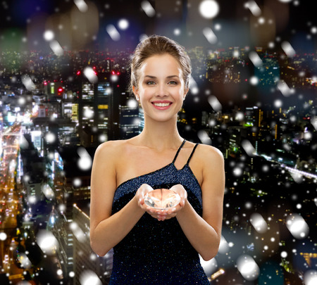 people, christmas, winter holidays and glamour concept - smiling woman in evening dress with diamond over snowy city background photo