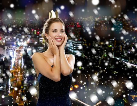 christmas crown: las personas, las vacaciones, la realeza y el concepto de Navidad - mujer sonriente en vestido de noche con la corona de oro sobre fondo cubierto de nieve la noche de la ciudad