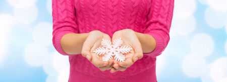 christmas, holidays and people concept - close up of woman in pink sweater holding snowflake over blue lights background photo