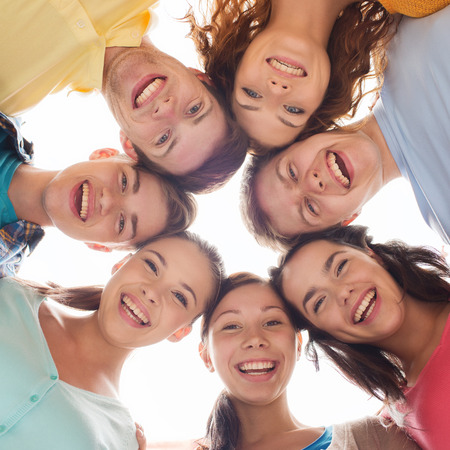 niñas sonriendo: la amistad, los jóvenes y las personas - grupo de adolescentes sonrientes en círculo
