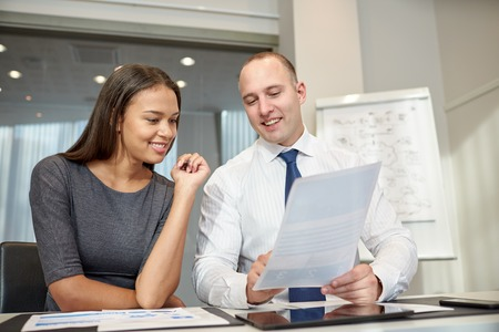 business, people and teamwork concept - smiling businessman and businesswoman with papers meeting in office photo