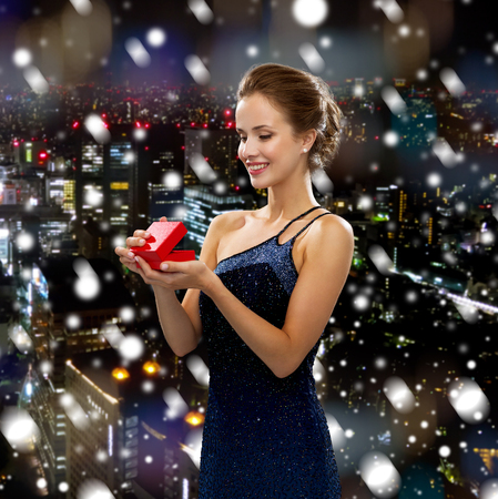 holidays, people and christmas concept - smiling woman in dress holding red gift box over snowy night city background photo