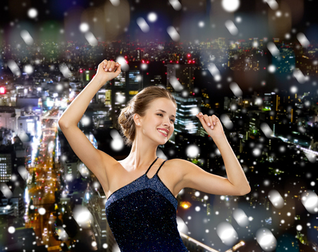 people, party, holidays and christmas concept - smiling woman dancing with raised hands over snowy night city background photo