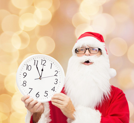 twelve month old: christmas, holidays and people concept - man in costume of santa claus with clock showing twelve over beige lights background