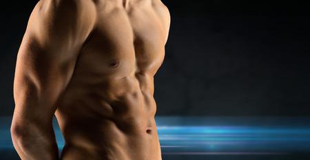 male torso: sport, bodybuilding, strength and people concept - close up of male bodybuilder bare torso over dark background