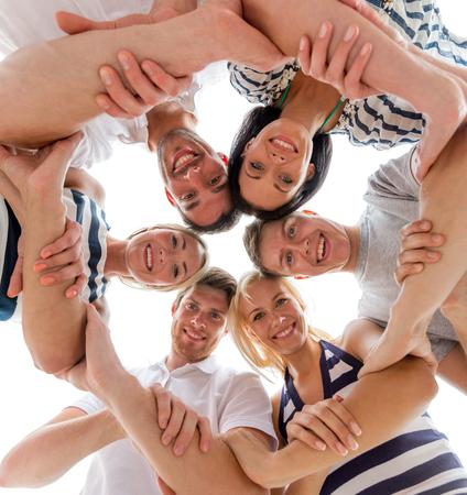 manos unidas: la amistad, la felicidad y concepto de la gente - amigos sonrientes en círculo