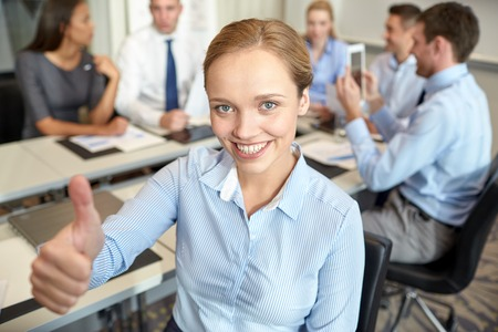 business, people, gesture and teamwork concept - smiling businesswoman showing thumbs up with group of businesspeople meeting in office photo