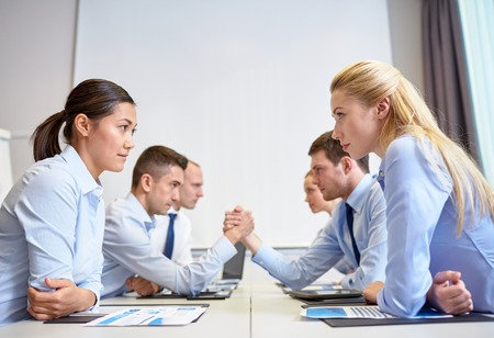 sides: business, people, crisis and confrontation concept - smiling business team sitting on opposite sides and arm wrestling in office