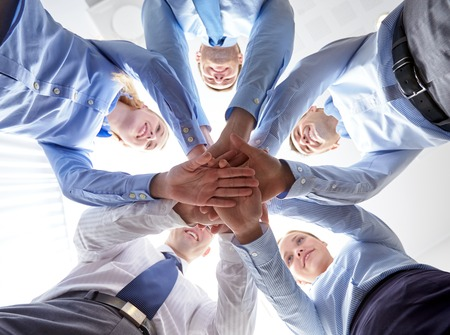 笑顔サークルに立って、互いの上に手を置くビジネスマンのグループ - ビジネス、人々 とチームワークの概念
