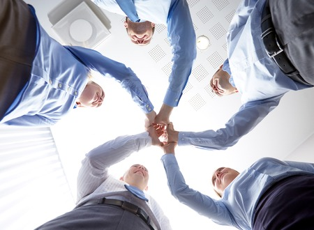 high five: business, people and teamwork concept - smiling group of businesspeople standing in circle and making high five gesture Stock Photo