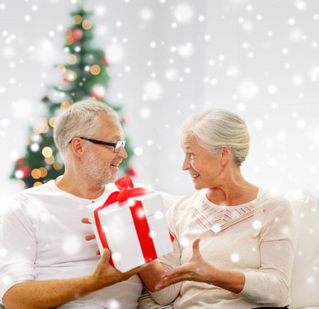 christmas ,family, holidays, age and people concept - happy senior couple with gift box and snow photo