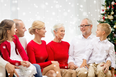 family, holidays, generation, christmas and people concept - smiling family sitting and talking on couch at home photo