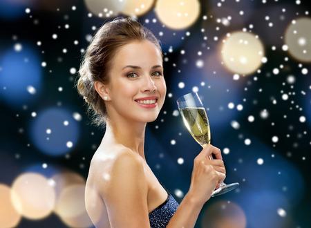 パーティー、ドリンク、祝日、クリスマスと人々 のコンセプト - 夜景と雪でスパーク リング ワインのグラスとイブニング ドレスの女性を笑顔