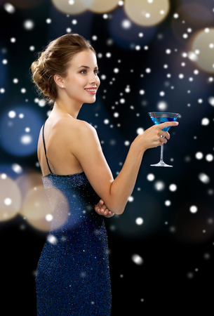party, drinks, holidays, christmas and people concept - smiling woman in evening dress holding cocktail over night lights and snow