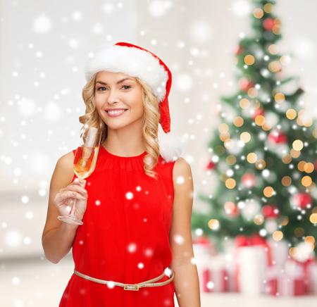 パーティー、ドリンクお祝いや人々 のコンセプト - リビング ルームとクリスマス ツリーの背景にサンタ ヘルパー帽子とシャンパン グラスで赤いド 写真素材
