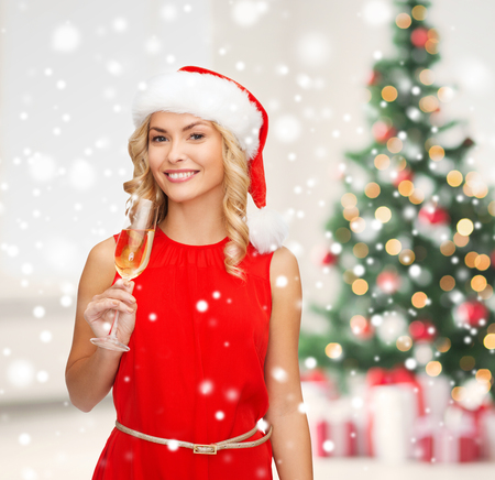 party, drinks celebration and people concept - smiling woman in santa helper hat and red dress with glass of champagne over living room and christmas tree