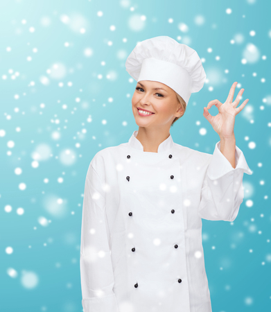 christmas cooking: christmas, cooking, profession, gesture and people concept - smiling female chef showing ok hand sign over blue snowy
